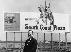 Photo of Henry Segerstrom in front of the South Coast Plaza sign in the early 1960s as construction had just begun.
